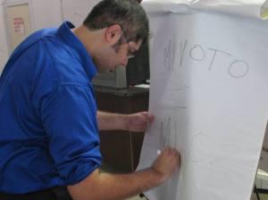 Jose Chapa, Equal Voice Civic Participation Coordinator for the RGV, writes the GOTV slogan: Mi Voto = Mi Voz