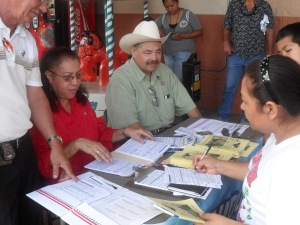 Member Sergio Narvaez, Director Juanita Valdez-Cox and member Don Francisco Martinez help a Junior's customer register to vote