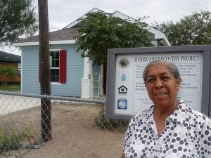 Doña Maria Gomez poses in front of her new home constructed with disaster recovery funds